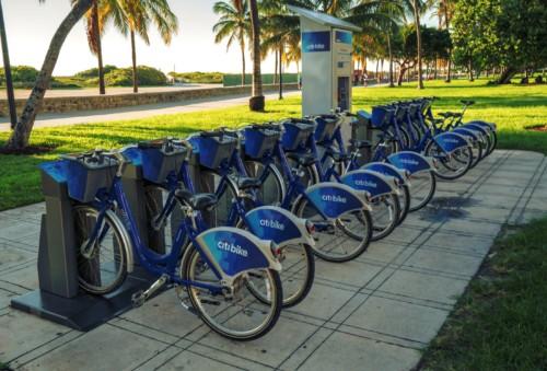 https://suiteness.imgix.net/destinations/miami/bigstock-miami-beach-citi-bike-station-106093034.jpg?mono=33EBC862&blend=2A303F&shad=90&gam=20&auto=format,compress